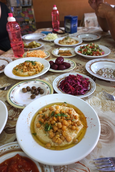 """A typical Israeli lunch includes pita bread with hummus- a mashed chickpea spread; Falafel- deep fried balls of chickpeas, onions and some other ingredients, usually served in pita bread; Shnitzel- fried chicken cutlets, served with hummus and ketchup; Baba Ganoush- an eggplant spread and often Shwarma: grilled meat, typically lamb, which is usually """"shaved"""", often enjoyed in pita or laffa bread. Add to that various fresh pickled vegetables, all served family style. It's a colorful table that encourages conversation."""